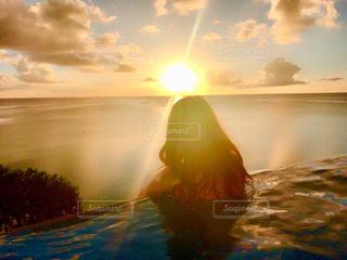 バック グラウンドで夕日を持つ男の写真・画像素材[961314]