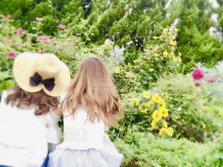 花の前に立っている女性の写真・画像素材[1181364]