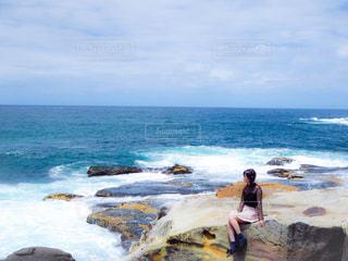 海の横にある水の体の横に立っている人 - No.1223823