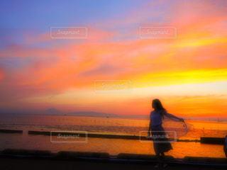 背景の夕日とビーチを歩いて男の写真・画像素材[1273062]