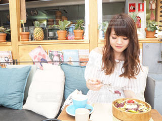 食物と一緒にテーブルに座っている女性の写真・画像素材[1644836]
