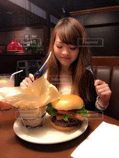 食品のプレートをテーブルに座っている女性の写真・画像素材[1651137]