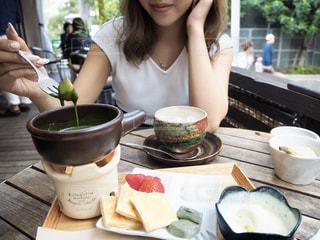 食物と一緒にテーブルに座っている女性の写真・画像素材[1651138]