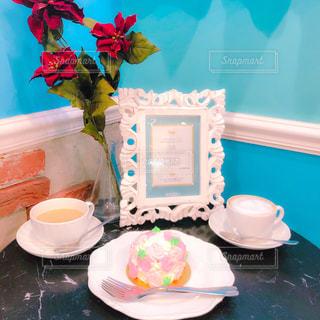一杯のコーヒーとテーブルの上の花の花瓶の写真・画像素材[1669382]