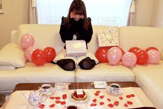 ケーキでテーブルに座っている人の写真・画像素材[1669660]