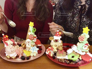ケーキでテーブルに座っている女性の写真・画像素材[1673600]