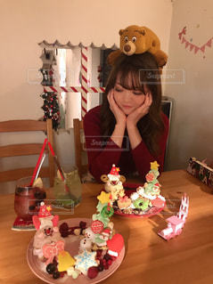 ケーキでテーブルに座っている少女の写真・画像素材[1673601]