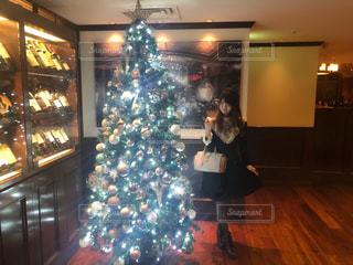 クリスマス ツリーの前に立っている人の写真・画像素材[1688280]