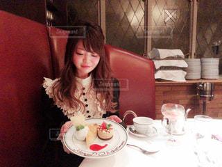 食事のテーブルに座っている女性の写真・画像素材[1688285]