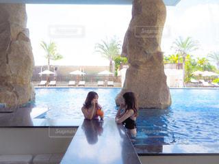 背景に水がある窓の前に立っている女性の写真・画像素材[2202243]