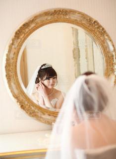 鏡の前に立つ人がカメラに向かってポーズをとるの写真・画像素材[2461660]