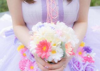 花を手にテーブルに座っている女性の写真・画像素材[3084251]