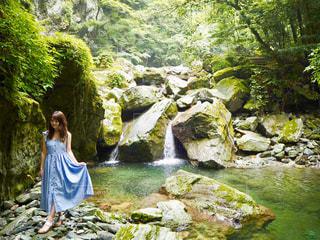 滝の隣に立っている人の写真・画像素材[3141622]