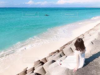 海の隣の砂浜に座っている人の写真・画像素材[3247771]
