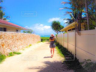 家の前の未舗装の道路を歩いている人の写真・画像素材[3247808]