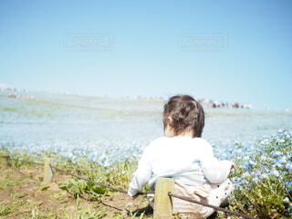芝生で覆われた畑の上に座っている男の写真・画像素材[4357085]