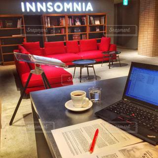 テーブルの上に座って赤いノート パソコン - No.929839