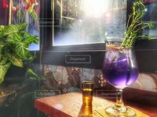 グラスのワインやテーブルの上に花の花瓶の写真・画像素材[929852]