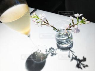 一杯のコーヒーとテーブルの上の花の花瓶 - No.929986