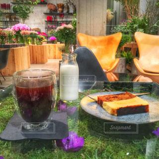 ピクニック用のテーブルの横にあるオレンジ ジュースのガラス - No.930538