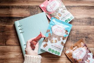 テーブルの上のチョコレートとノートの写真・画像素材[3964124]