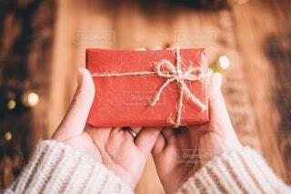 赤い包み紙のプレゼントと手の写真・画像素材[3996770]