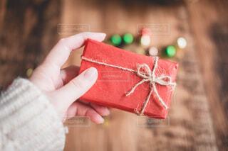 赤いプレゼントを持つ手の写真・画像素材[3996780]