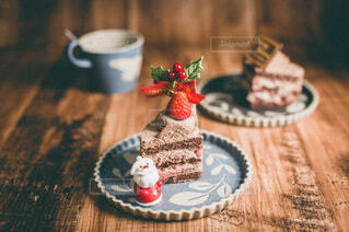 木製テーブルの上にケーキとカップの写真・画像素材[4000390]