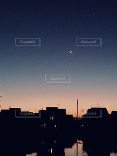 朝焼けと池と月の写真・画像素材[3786876]