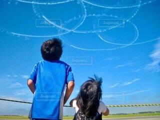 青空に描かれたブルーインパルスのスモークを見る子供の写真・画像素材[3977252]