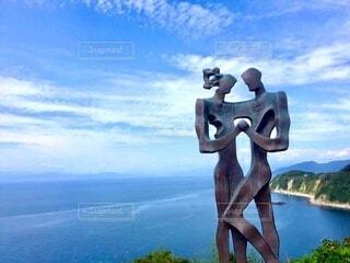 青空と海をバックにした男女の彫刻の写真・画像素材[3977307]