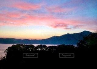 海と山を背景にピンクに染まる雲の夕暮れの写真・画像素材[3995825]
