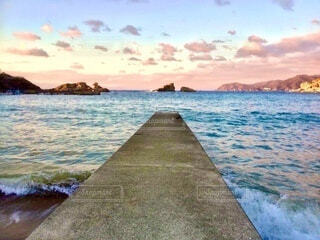 海岸沿いの夕暮れと波打ち際の橋の写真・画像素材[3995832]