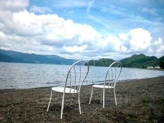 湖の湖畔に置いてある二脚の椅子の写真・画像素材[4005416]
