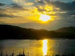 海の背景にある山から昇る朝日の写真・画像素材[4071868]