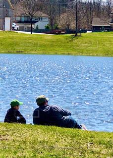 輝いく水面の前でくつろぐ男性と男の子の写真・画像素材[4303038]