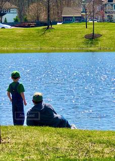 きらめく池の手前に横たわる男性と男の子の写真・画像素材[4303042]