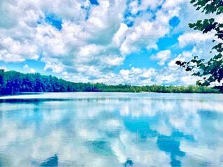 背景を山にした湖に映る雲の写真・画像素材[4432787]