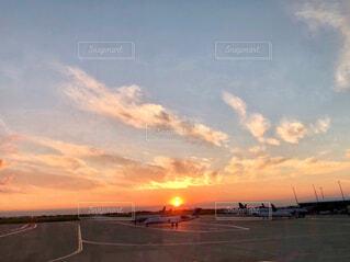空港の飛行機の滑走路の後ろから昇る朝日の写真・画像素材[4614810]