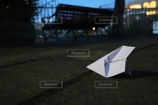 ベンチの前に落ちた紙飛行機の写真・画像素材[3820994]