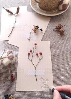 クッキーに植物を貼ったメッセージカードを添えるの写真・画像素材[4042077]