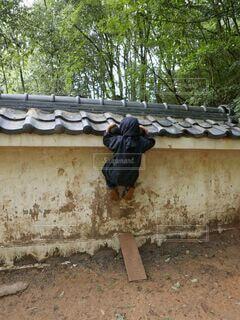忍者の格好で塀を登る子供の写真・画像素材[4125655]