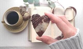 チョコレートをかけたクッキーを持つ手の写真・画像素材[4201634]