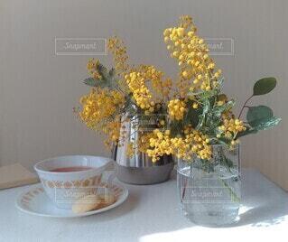 デーブルの上のミモザを生けた花瓶の写真・画像素材[4207450]