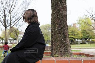 木の横でコートを着て座る女性の写真・画像素材[3841072]