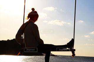海に向かってブランコに座って夕日を浴びる女性の写真・画像素材[3845339]