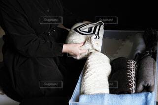 ニットを衣装ケースに入れる女性の写真・画像素材[3854526]