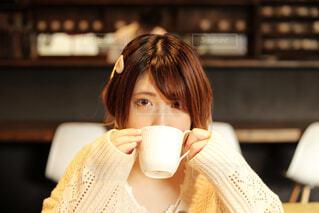 コーヒーを飲みながら座っている女性の写真・画像素材[3881388]