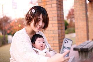 スマートフォンで赤ちゃんと一緒に自撮りをする女性の写真・画像素材[3881389]