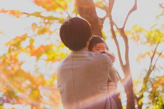紅葉の前で赤ちゃんを抱く男性の写真・画像素材[3910992]